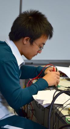 Un apprenti en CAP Electricien est penché sur sa table de travail, entre des instruments de mesure et des feuilles de note.