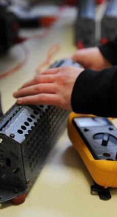 Deux mains de jeune apprenti paramètrent un multimètre.