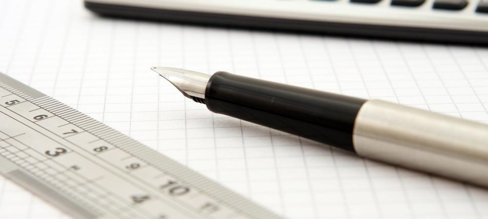 Gros plan sur un stylo, un cahier aux pages blanches, et une calculatrice.