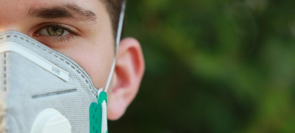 Un jeune homme pose avec un masque sanitaire sur le visage, nous ne voyons que la moitié gauche de son visage ; un droite un fond flou de verdure.
