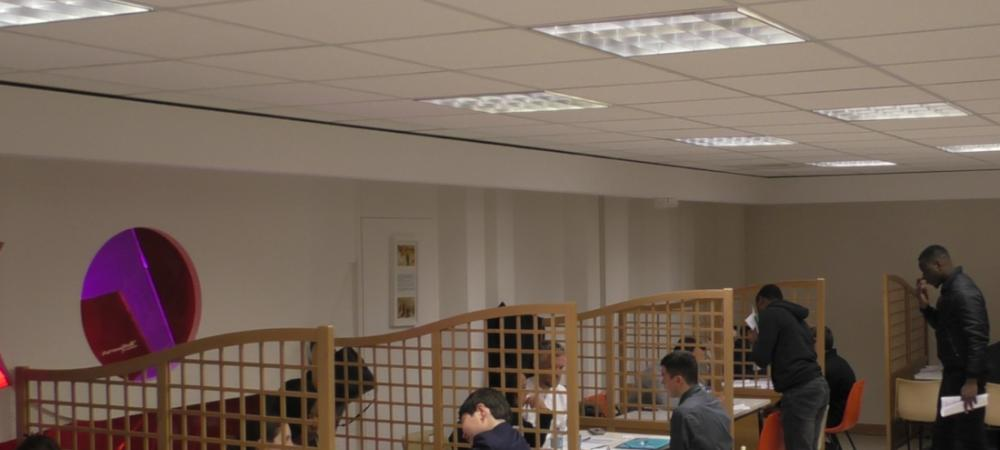 Dans le réfectoire du CFA Delépine, des recruteurs et des candidats sont face à face sur plusieurs tables alignées.