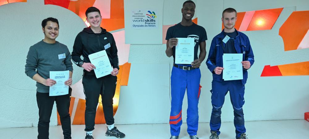 Les quatre compétiteurs de l'épreuve régionale des Worlds Skills 2020 métier électricien posent avec leurs diplômes devant le vitrail du CFA Delépine.